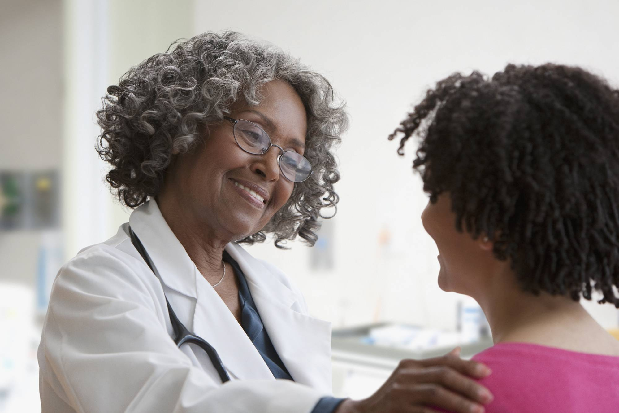 Smiling nurse talking with patient.